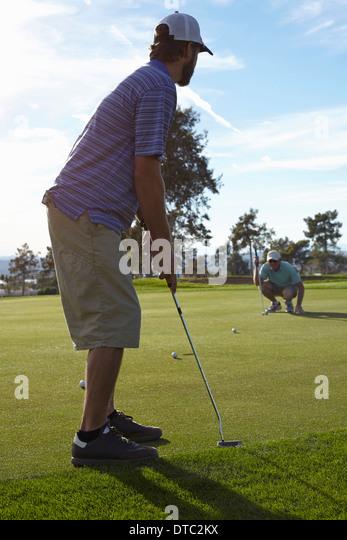 Zwei männliche Golfer Schlange Schuss auf grün Stockbild