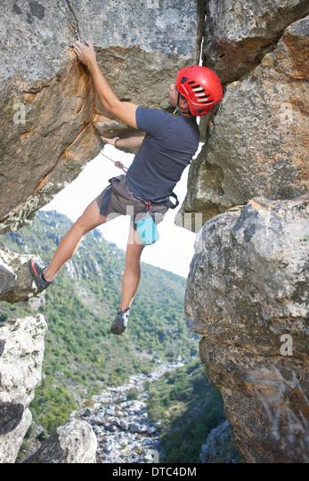 Junge männliche Kletterer balancing und halten Seil Stockbild