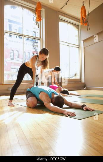 Yoga-Lehrer, die Unterstützung von Menschen in der Klasse Stockbild