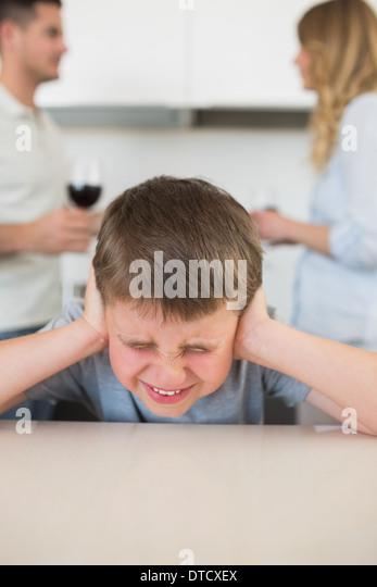 Furstrated junge für Ohren, während die Eltern streiten Stockbild