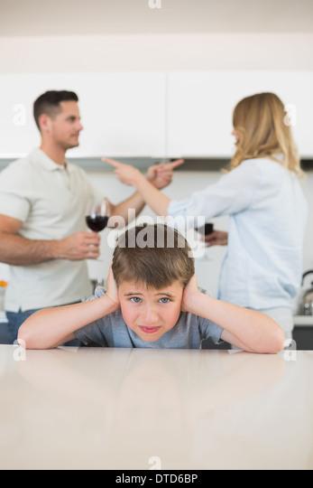 Junge für Ohren, während die Eltern streiten Stockbild