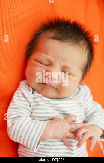 Ein Baby in einem gestreiften Oberteil mit seinen Augen geschlossen liegend auf einer orange Kissen Pennsylvania Stockbild