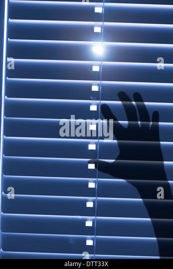 Konzeptbild, gefangen und hilflos. Schatten eines Blatts für geschlossene Fenster-Vorhänge mit Sonnenlicht Stockbild