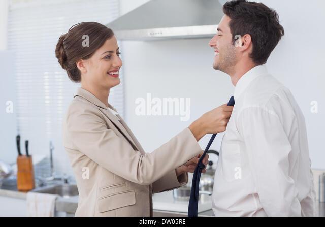 Frau, die helfen, ihr Ehemann, seine Krawatte zu binden Stockbild