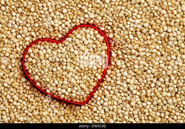 Rotes Herzform auf rohem Quinoa Hintergrund Stockbild