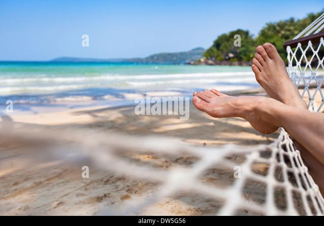 Frau Fuß in der Hängematte am Strand Stockbild