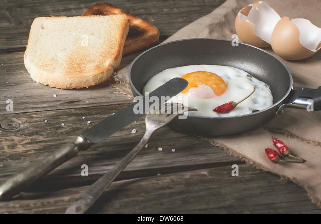 Frühstück mit Spiegelei auf Pfanne serviert mit Toast, red hot Chili Peppers und Vintage Geschirr über Stockbild