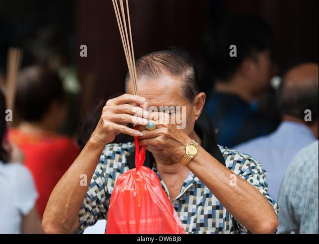 Buddhisten beten und Weihrauch bei Kwan Im Thong Hood Cho Tempel in Singapur. Stockbild