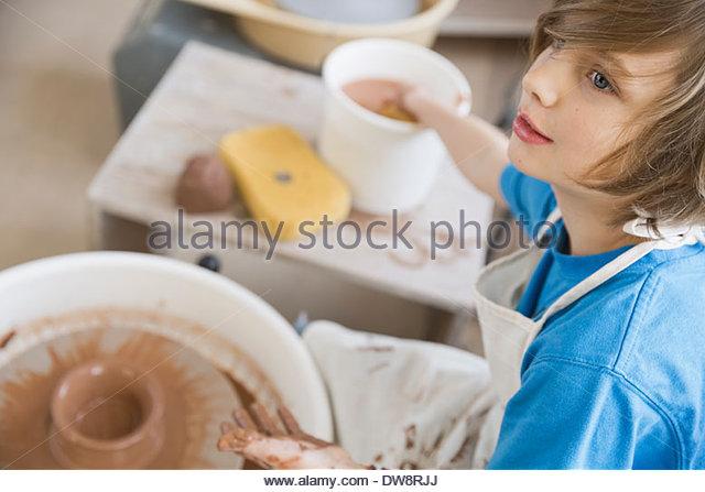 Junge mit Töpferscheibe im Kunstunterricht Stockbild
