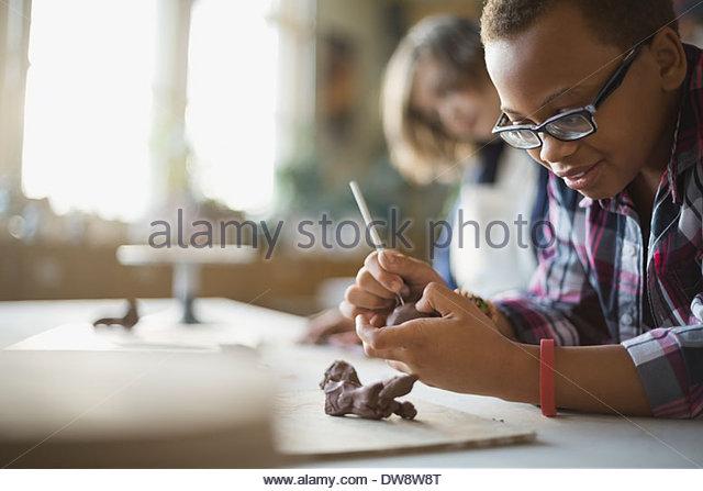 Junge erstellen Tonfiguren im Kunstunterricht Stockbild