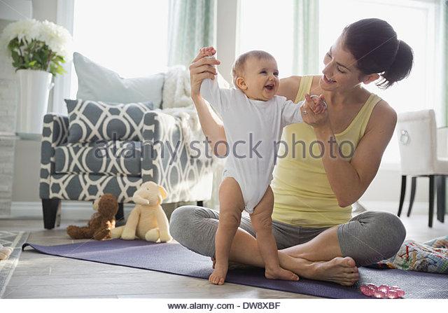 Mutter mit Baby auf Yoga-Matte zu Hause spielen Stockbild