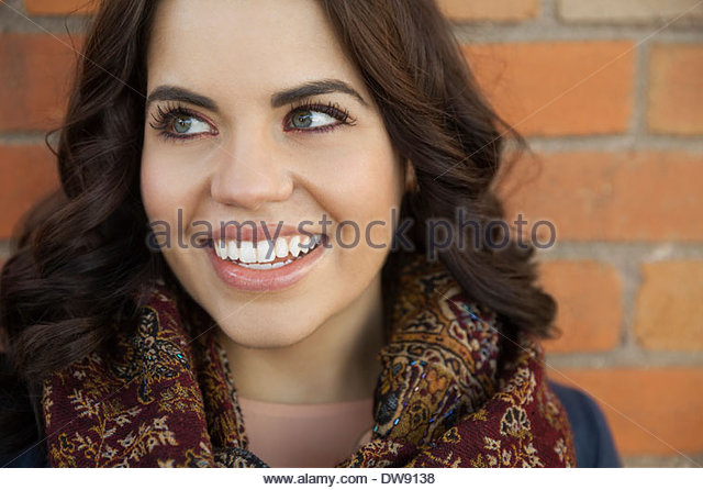 Schöne Frau lächelnd gegen Mauer Stockbild