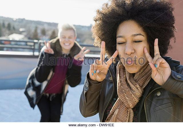 Verspielte Frau, die Peace-Zeichen im freien Stockbild