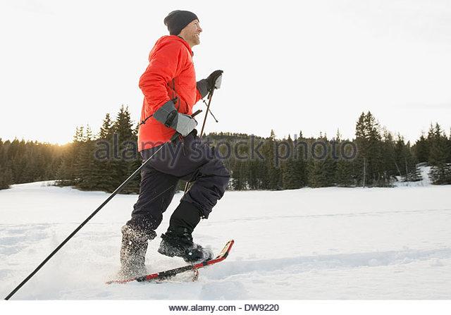 Seitenansicht des Mannes Schneeschuhwandern Stockbild