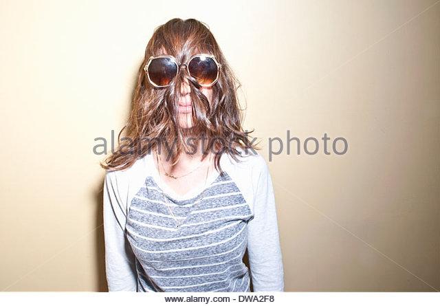 Frau mit Sonnenbrille mit braunen Haaren bedeckte Gesicht Stockbild