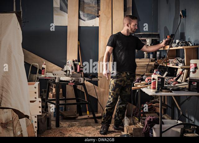 Männliche Zimmermann Suche Regale in Werkstatt Stockbild