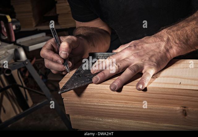 Nahaufnahme eines männlichen Zimmermann mit Geodreieck in Werkstatt Stockbild