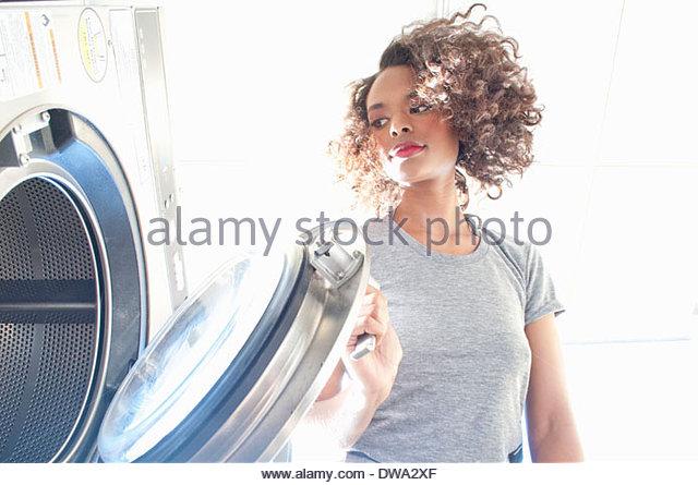 Junge Frau im Waschsalon, Eröffnung Trockner Wäsche überprüfen Stockbild