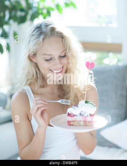 Schöne Frau mit Himbeer Kuchen mit Gabel im Haus Stockbild