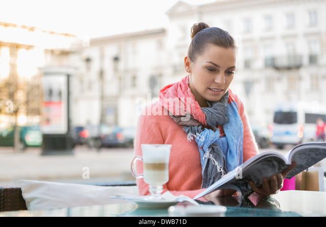 Junge Frau Lesebuch im Straßencafé Stockbild