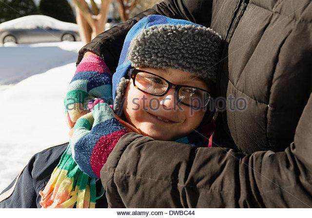 Mutter umarmt Sohn mit Winter Hut und Brille Stockbild