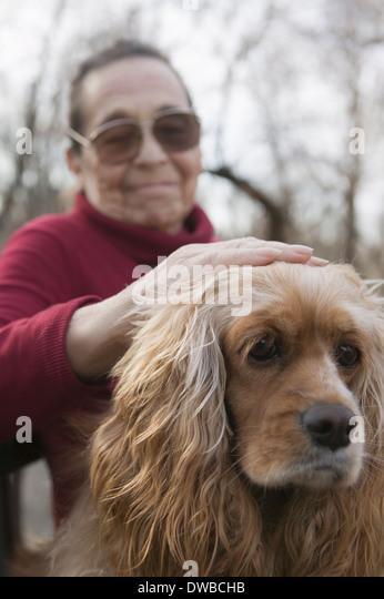 Ältere Frau tätschelte Hund Stockbild