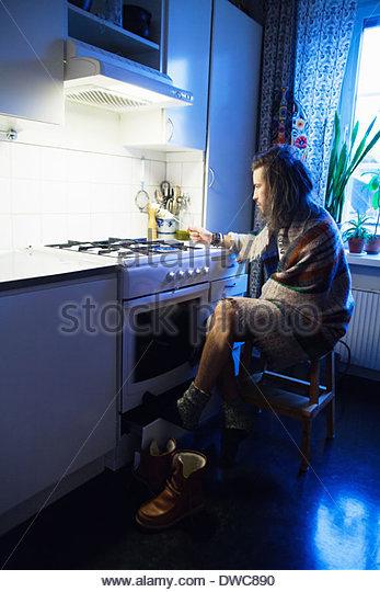 Mitte erwachsenen Mannes in Decke gehüllt Rösten Marshmallows in Küche Stockbild