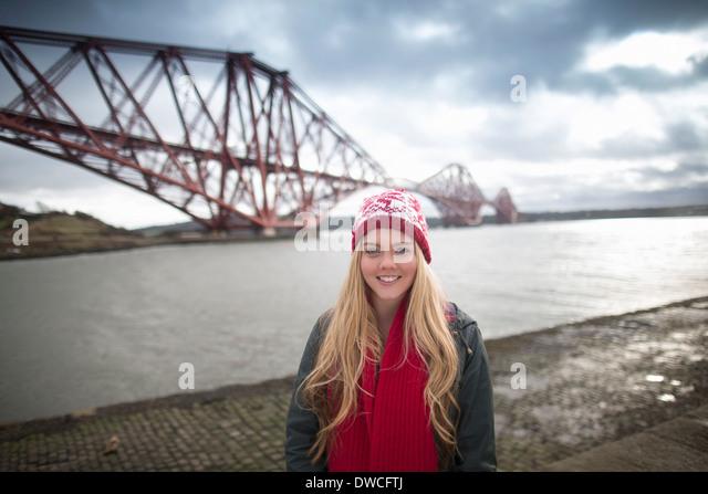 Eine junge Womans posiert vor der Forth Rail Bridge in Queensferry, in der Nähe von Edinburgh, Schottland Stockbild