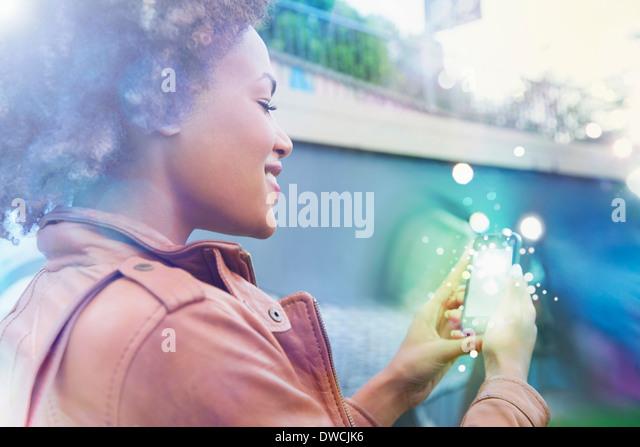 Junge Frau mit leuchtende Lichter kommen aus Smartphone betrachten Stockbild