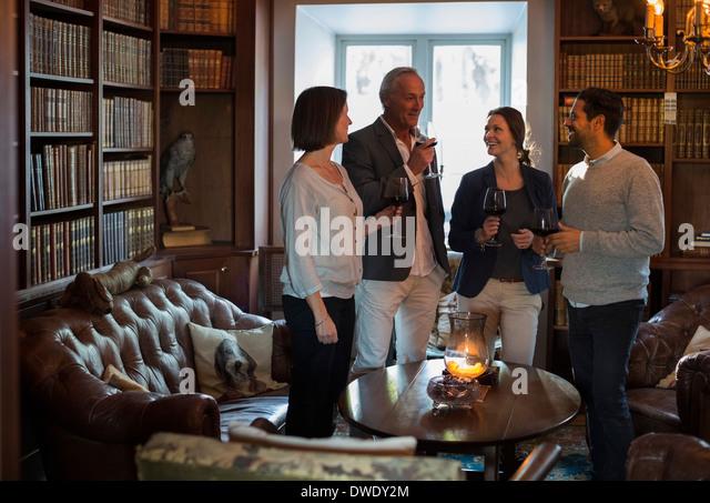 Geschäftsleute mit Weingläsern, die Freizeit zu verbringen, in Restaurant lobby Stockbild