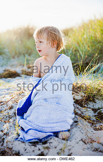 Voller Länge des jungen gewickelt in Handtuch am Strand zu entspannen Stockbild