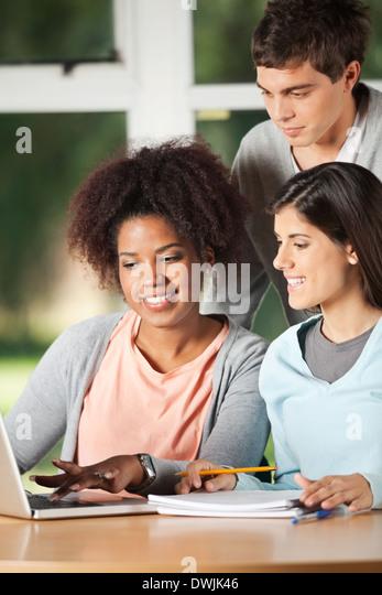 Freunde mit Laptop am Schreibtisch im Klassenzimmer Stockbild