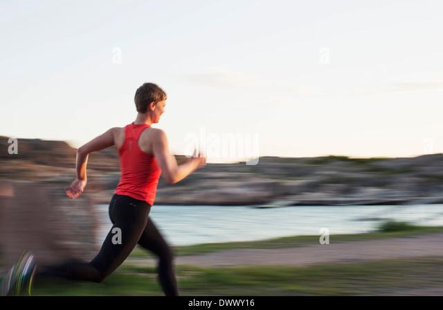 Bewegungsunschärfe von Frau läuft am Seeufer Stockbild