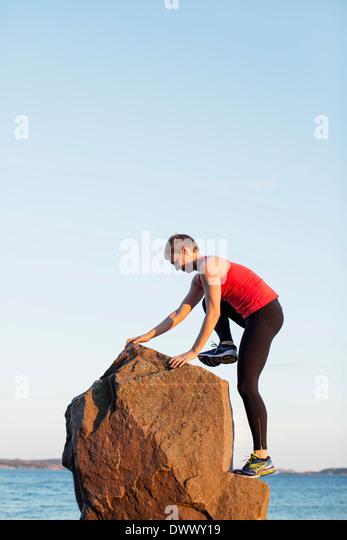Gesamte Länge der sportlichen Frau Klettern auf Felsen gegen klaren Himmel Stockbild