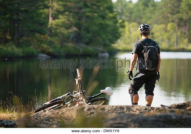 Rückansicht des Mountainbiker Blick auf See Stockbild