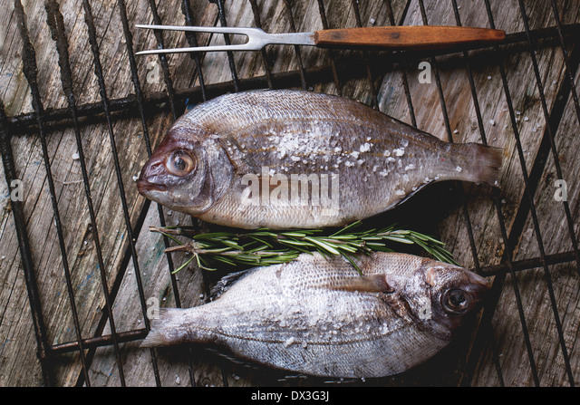 Draufsicht auf Schlepptau Rohfisch Brassen mit Rosmarin und Meer Salz auf Grill über alten Holztisch. Stockbild