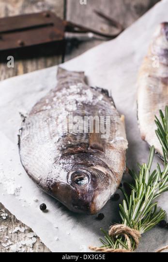 Dorado Rohfisch mit Rosmarin und Meer Salz Server auf weißem Papier über alten Holztisch. Stockbild
