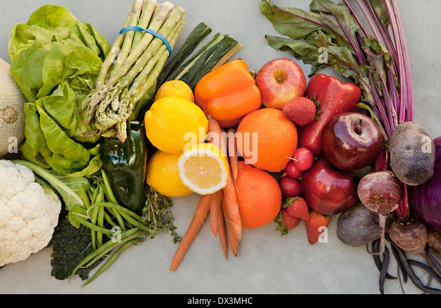 Reichlich Auswahl an mehrfarbigen Obst und Gemüse direkt oberhalb von Farbe auf grauem Hintergrund organisiert Stockbild