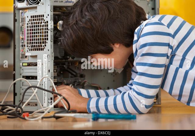 Kleiner Junge das Innere eines Computers mit großer Aufmerksamkeit zu erkunden Stockbild