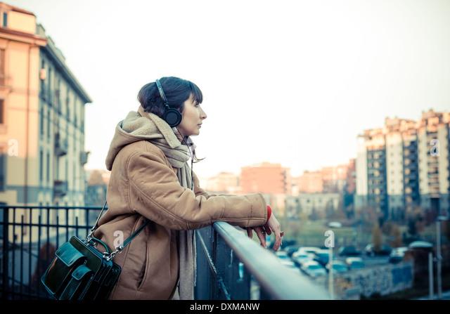 schöne junge Frau, hören Musik Kopfhörer in der Stadt-winter Stockbild