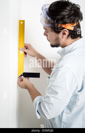 junger Mann Bricolage arbeiten mit Messgerät zu Hause messen Stockbild