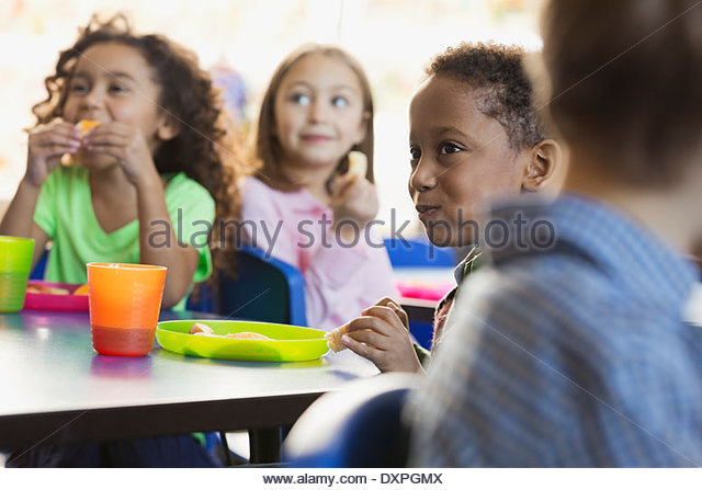 Kinder essen Snacks im Unterricht der Grundschule Stockbild