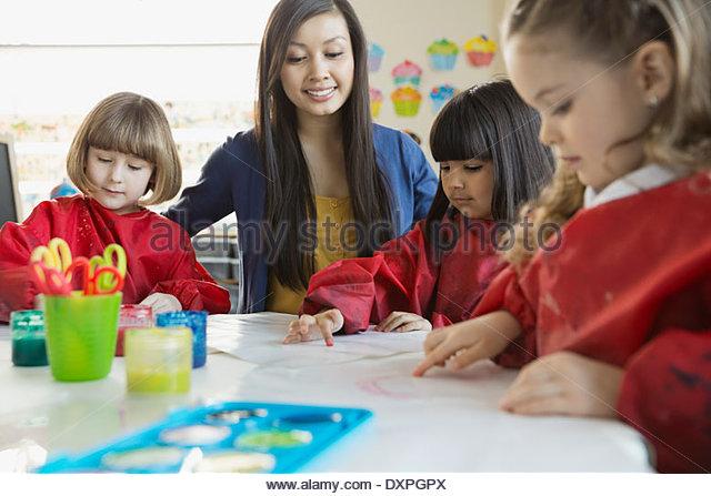 Lehrer mit Schülern im Kunstunterricht Stockbild