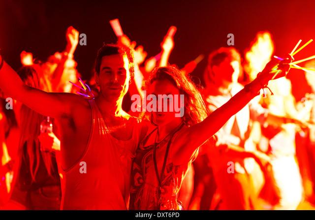 Porträt des Paares mit Leuchtstäben tanzen beim Musikfestival Stockbild