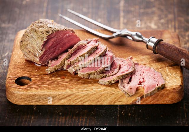 Roastbeef an Board und Fleisch Gabel schneiden Stockbild