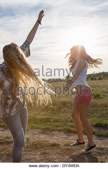 Zwei junge Frauen tanzen in Feld Stockbild