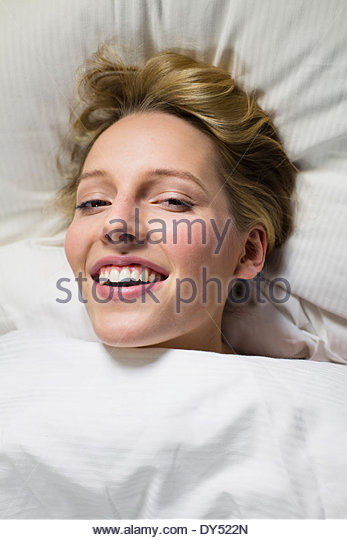 Junge Frau unter Bettdecke, Kopf auf Kissen Stockbild