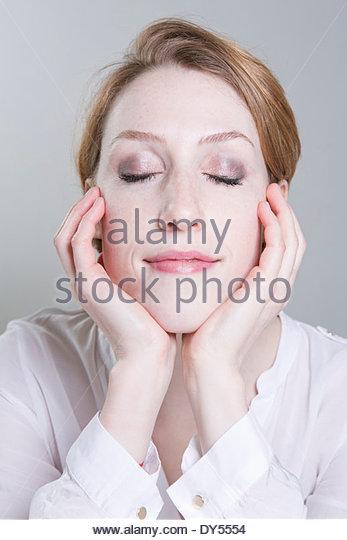 Porträt der jungen Frau, Kinn, Hände, Augen geschlossen Stockbild