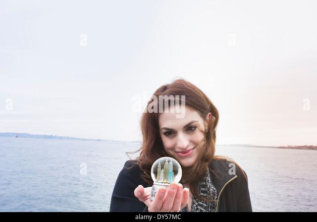 Junge Frau mit Wahrzeichen Schneekugel, New York, USA Stockbild