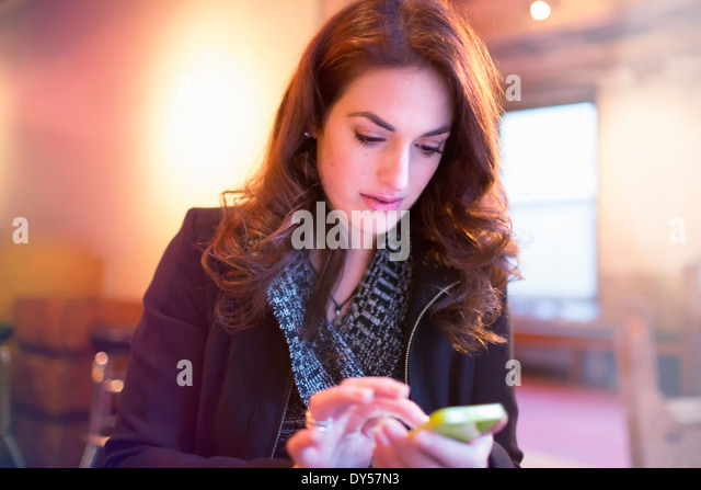 Junge Frau SMS auf Smartphone im café Stockbild